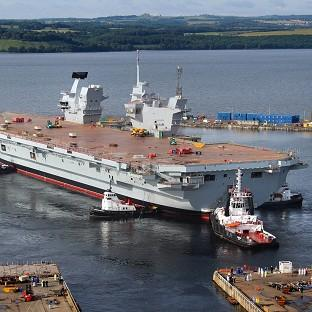 HMS Queen Elizabeth, the largest warship ever built in the UK, during her 'float out' of the dock at the Rosyth Doc