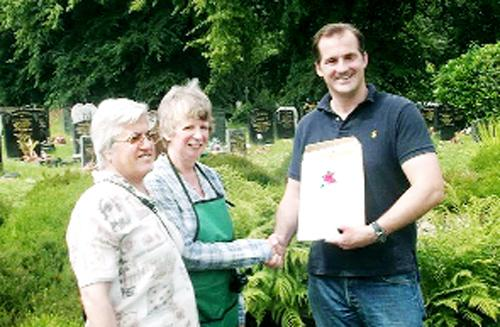 Darwen MP Jake Berry presents Anne Lamont with her volunteer award, watched by Coun Karimeh Foster