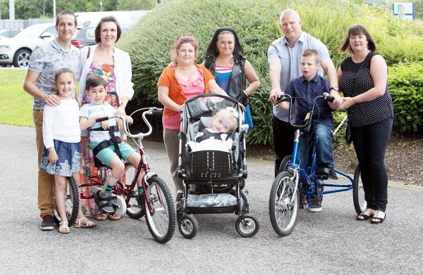 Three families helped by Children Today at the anniversary event, from left, Giovanni and Lisa Vaccaro with Francesca and Mario, Caroline Macdonald and her mum Emily with Angel-May, and Stephen and Sharon Hillyard with Reece, testing out a bike ahead of g
