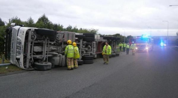 Firefighters attend the scene of the over-turned lorry. PIC: Blackburn Fire Service