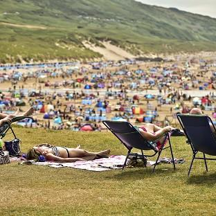 People relax in sunny weather at Woolacombe, North Devon, as the hot weather continues across the UK