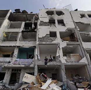 Palestinians inspect damaged buildings in a residential district of the town of Beit Lahiya, in Gaza (AP)