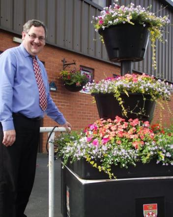 Councillor Adrian Lowe with one of the council's tower planters