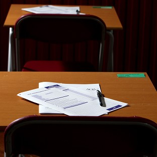 A primary school head teacher has been banned from the classroom after altering exam papers