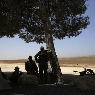 Israeli reserve soldiers watch near the Israel Gaza border (AP)