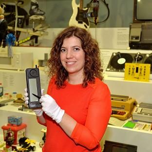 Charlotte Connelly of the Science Museum holds an IBM Simon mobile phone from 20 years ago