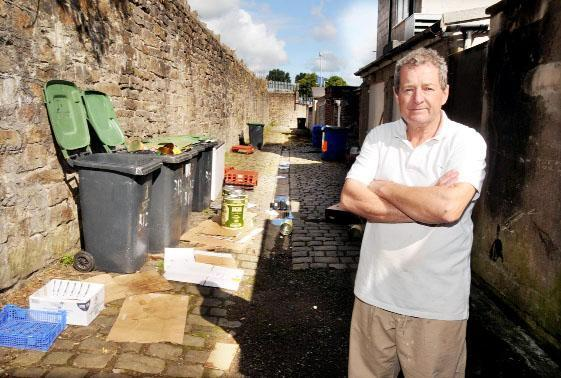 David Leaver with the rubbish left behind the bakery on Bolton Road