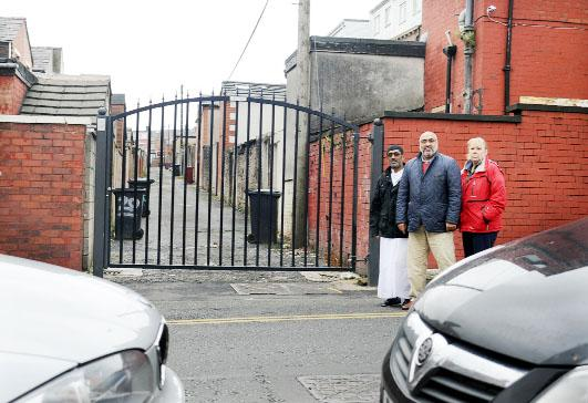 Coun Salim Sidat, centre with residents Abdul Mulla and Alison Robinson at the alley being blocked by cars