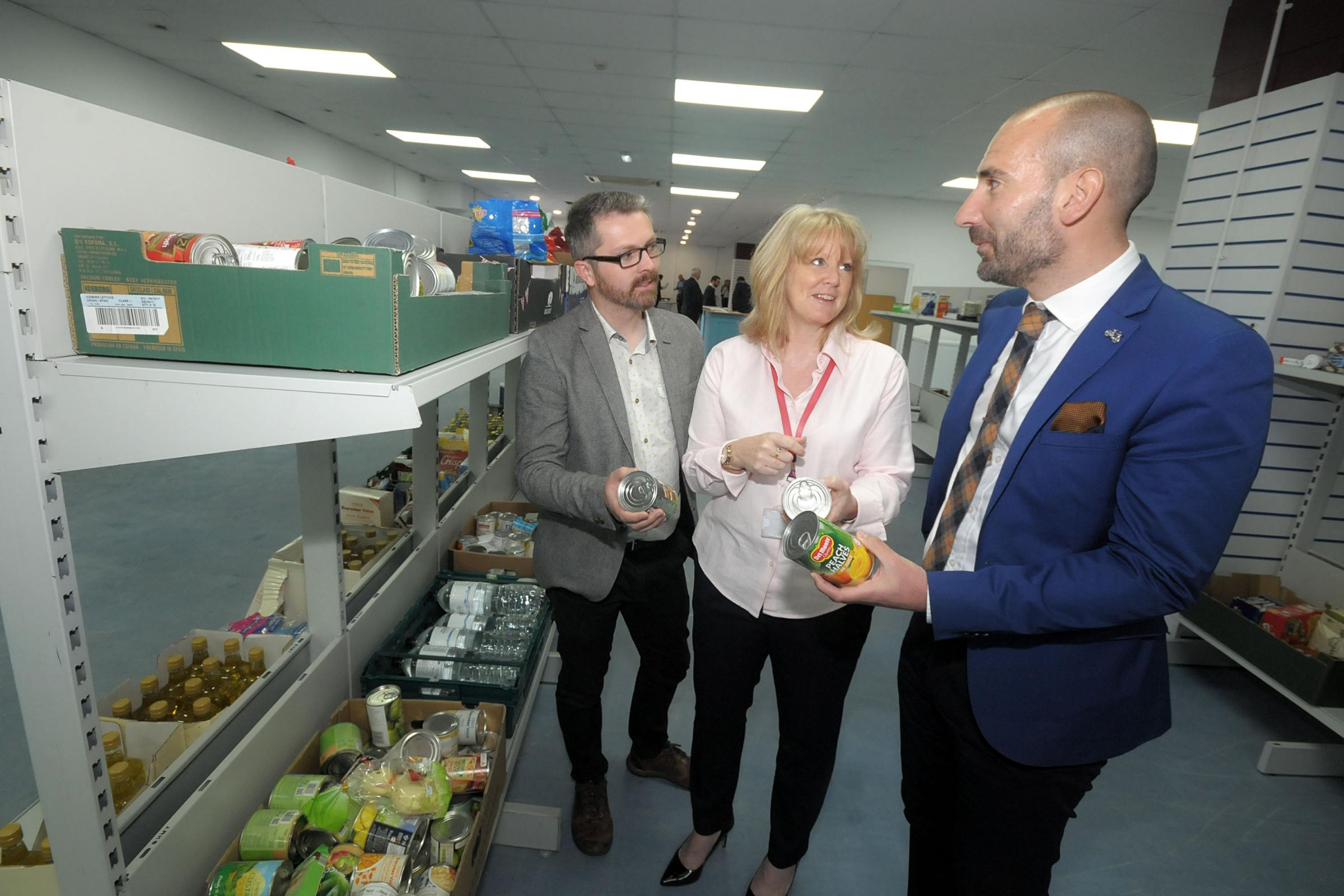 Burnley FC Kitchen opens for viewing as part of Burnley Business Week (pictured: Community Kitchen Manager Anita Orchard spaeks with council business support officer Martin Hardacre and PM&M Wealth Manager Neil Walsh in the food bank area)