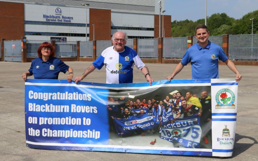 Pictured left to right are: Annette Birkbeck, Alan 'Birdy' Birkbeck and Cllr Jamie Groves with the Rovers promotion banner.