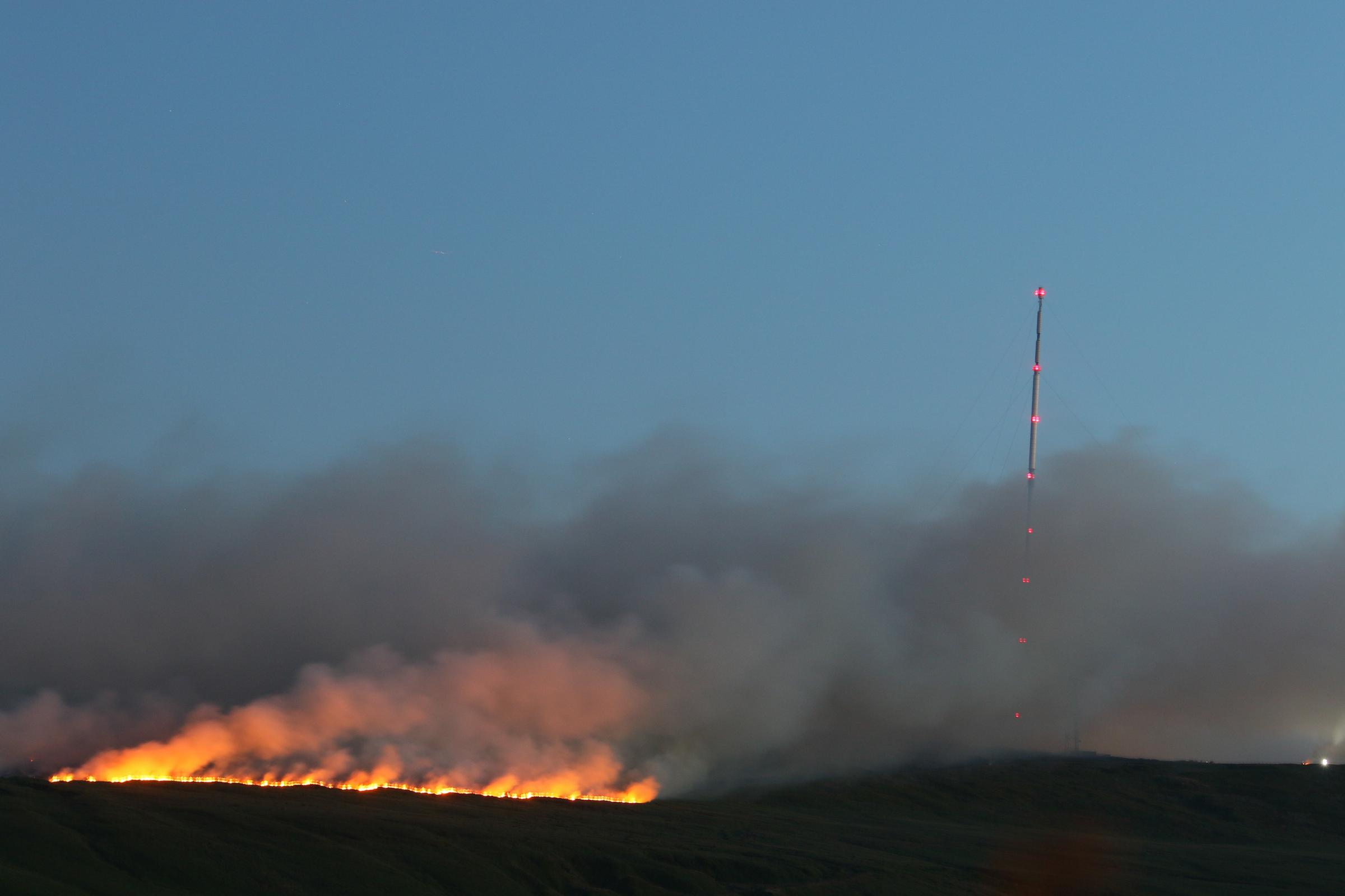 30 June 2018. Saturday. Moorland fire at Winter Hill, Bolton, Lancashire. The mast is the Winter Hill TV transmitter for North West England. Firefighterts allowed the fire to burn without control for safety reasons in the dark.Pictures by Phil Taylor Tel