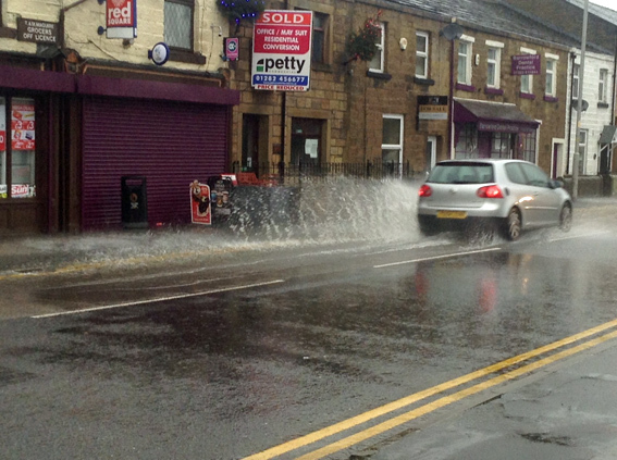 A car goes through a puddle in Barrowford.