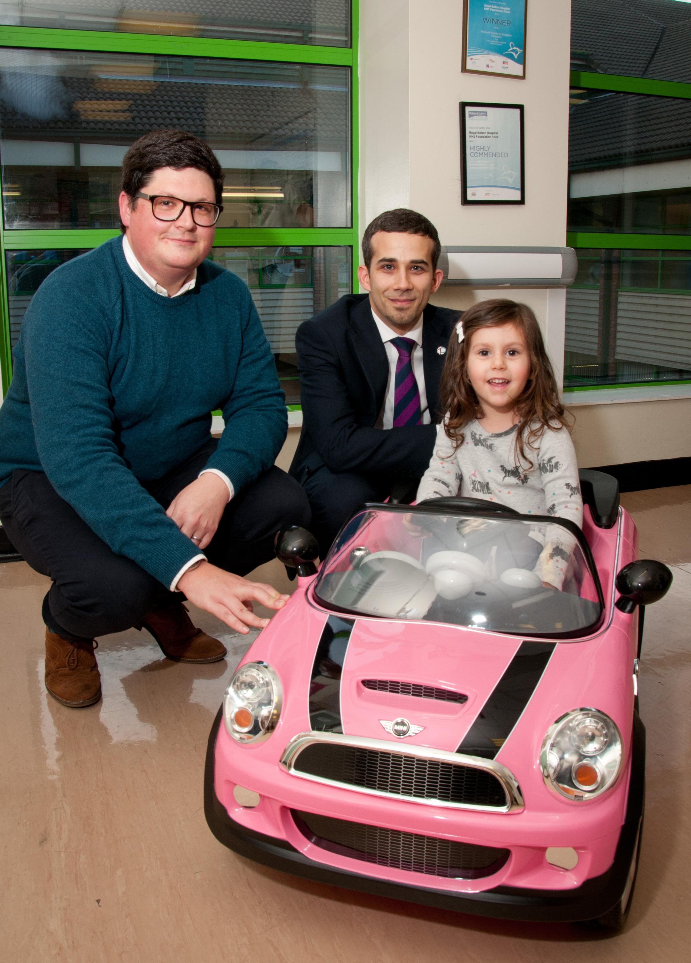 Little Lucy test drives a mini car accompanied by Dr Carl Oakden (left) and Kieran Anderson from Porsche Bolton