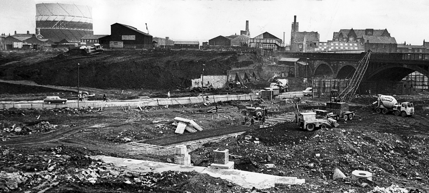A busy scene at Church Whaft. In the background, bulldozers carve the route of the new road which will run from Bury New Road beneath the railway arches (right) to link with Folds Road. In the foreground, the long pedestrian subway which will link Bury Ne